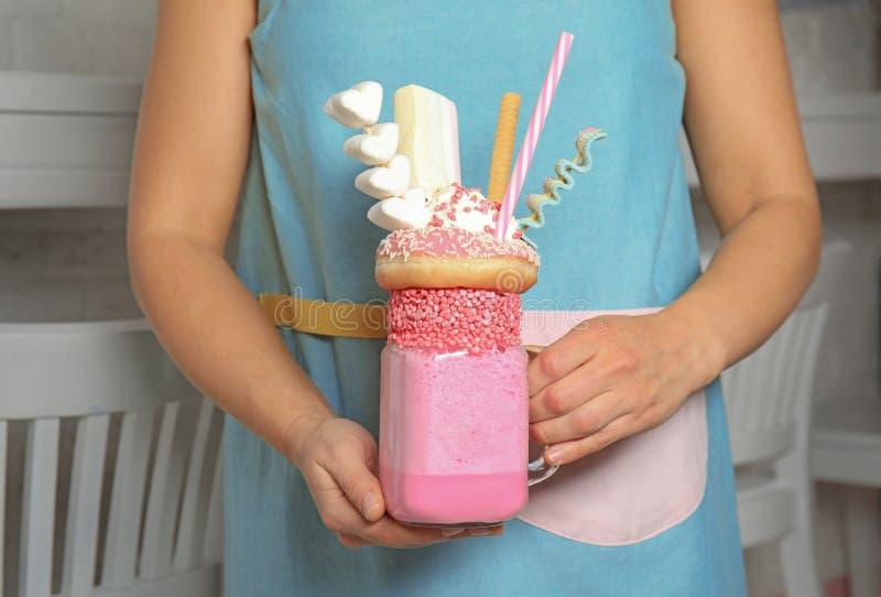 Frauenholdingweckglas des geschmackvollen Milchshakes mit Bonbons zuhause lizenzfreies stockbild