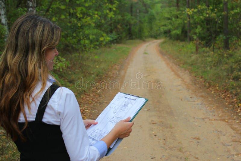 Fraueningenieur auf Waldweg mit Papierplan des Projektes des Baus stockfotografie