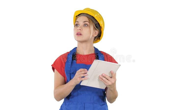 Fraueningenieur, der Bauplan auf Berührungsfläche überprüft und Gegenstände, Gebäude um sie auf weißem Hintergrund betrachtet stockfotografie