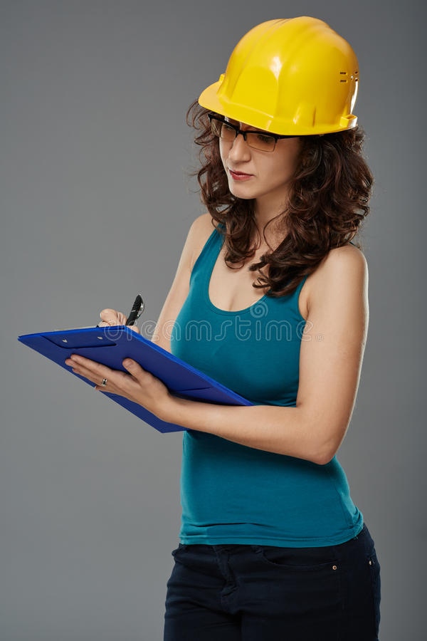 Fraueningenieur mit Schutzsturzhelm und -ordner stockbild