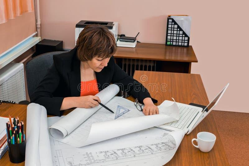 Fraueningenieur zeichnet Zeichnungen lizenzfreie stockbilder