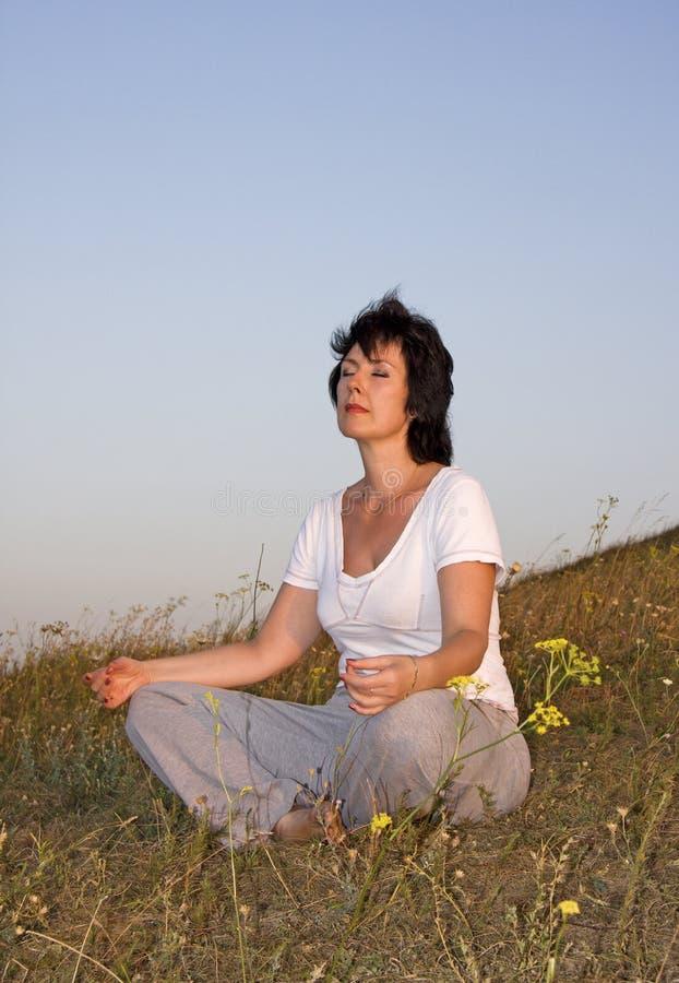 Fraueninteressen auf Yoga auf Sonnenuntergang des day.2. lizenzfreie stockfotos