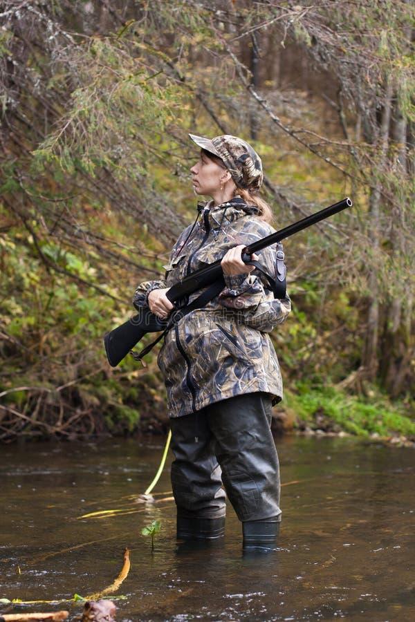 Frauenjäger auf kleinem Fluss im Wald stockfotos