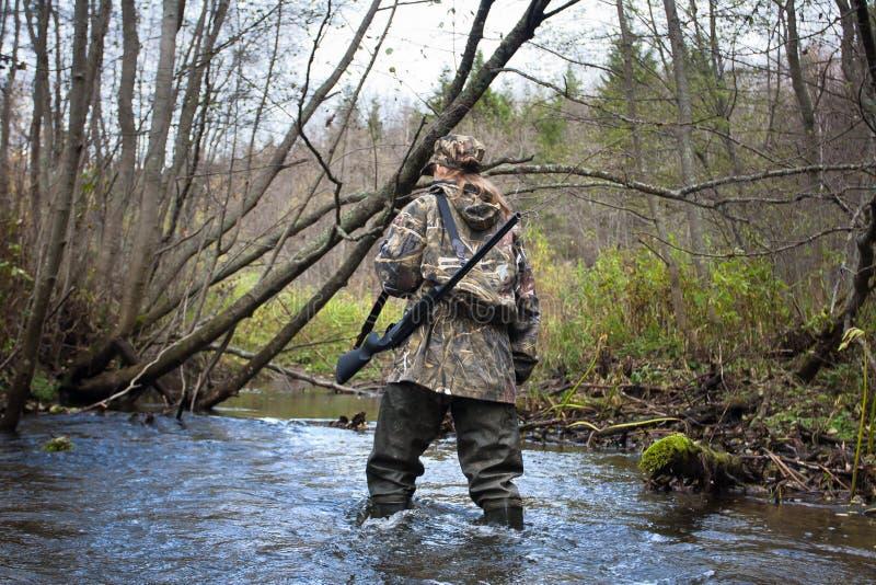 Frauenjäger in den Stelzvögeln, die kleinen Fluss im Wald kreuzen lizenzfreie stockfotos