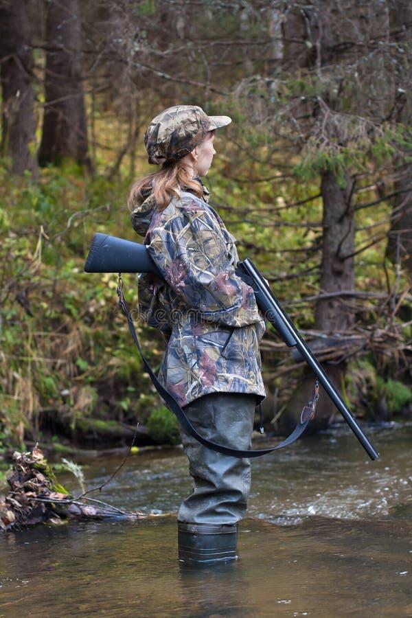 Frauenjäger, der auf Opfer auf kleinem Fluss im Wald aufpasst stockfotos