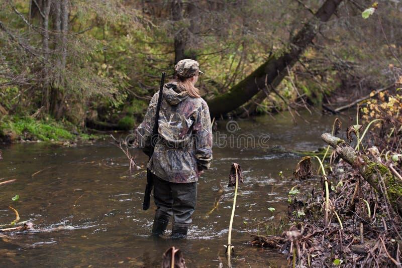 Frauenjäger, der den Fluss kreuzt lizenzfreies stockfoto