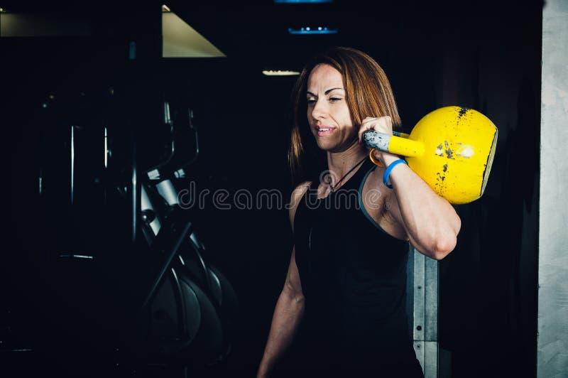 Frauenkessel-Glockentraining in der Turnhalle Muskulöse Frau, die Kesselglocke hält stockbilder