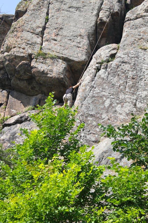 Frauenklettereraufstiege auf einem Felsen stockbild