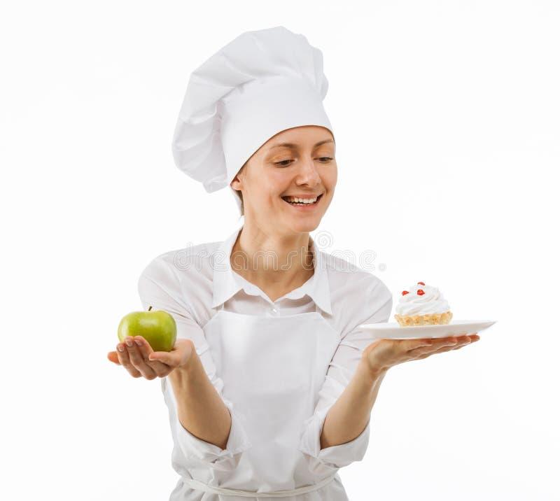 Frauenkoch wählt zwischen einem Apfel und einem Kuchen stockbild