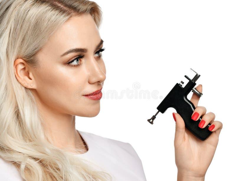 Frauenkosmetiker Cosmetologistgriff Ohr-Durchdringen-Gewehr, welches die Ecke lokalisiert auf Weiß betrachtet lizenzfreie stockfotos