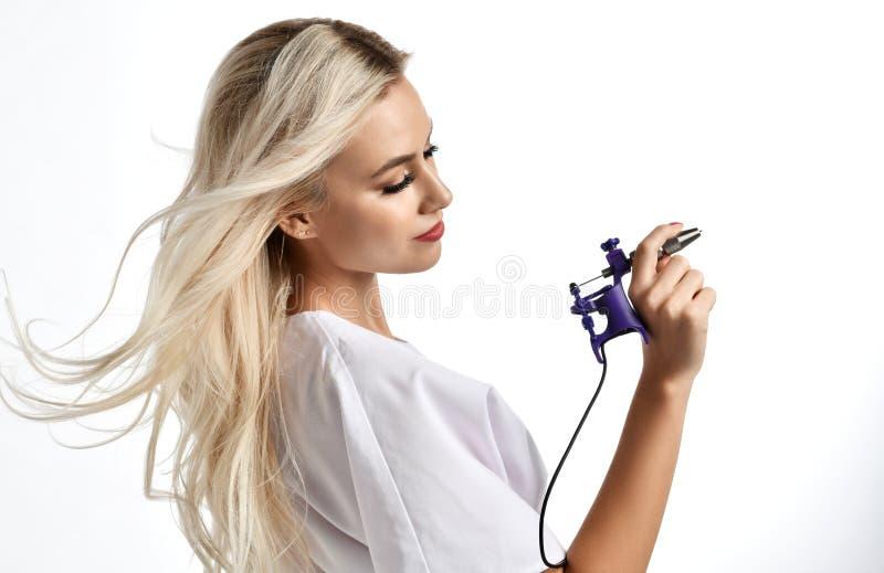 Frauenkosmetiker Cosmetologistgriff-Tätowierungsmaschinengewehr lokalisiert auf Weiß lizenzfreie stockbilder