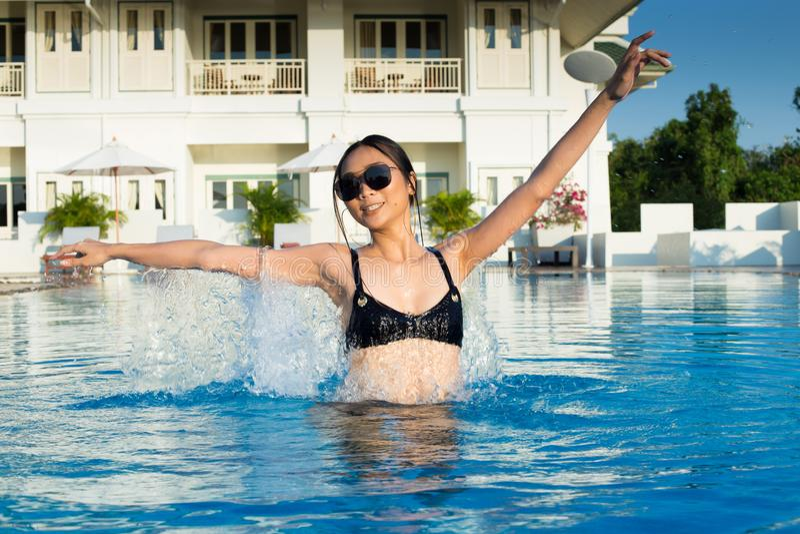 Frauenlächeln mit Wasserspritzen in der großen blauen Schwimmen stockfotografie