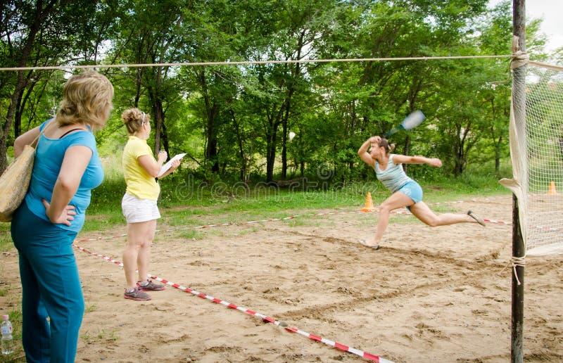 Frauenläufe, die versuchen, fliegenden Federball während der Amateurwettbewerbe von Strandtennis abzustoßen lizenzfreies stockbild