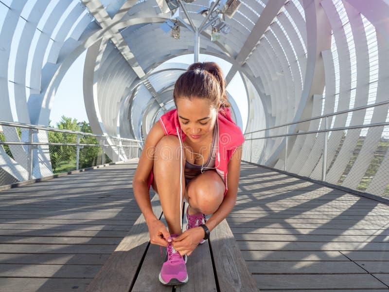 Frauenläufer, der Spitzee in der Stadt bindet stockfotos