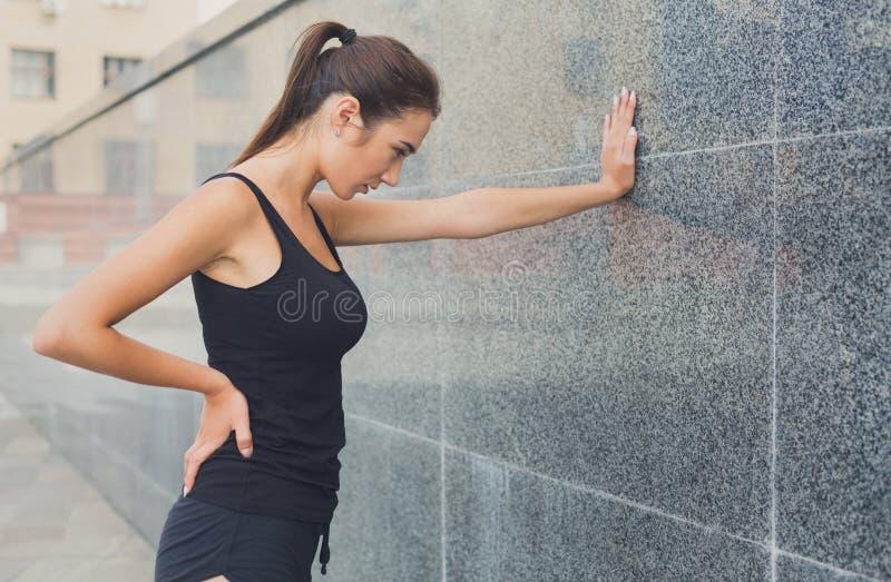 Frauenläufer hat den Bruch und lehnt sich auf grauer Wand stockfotos