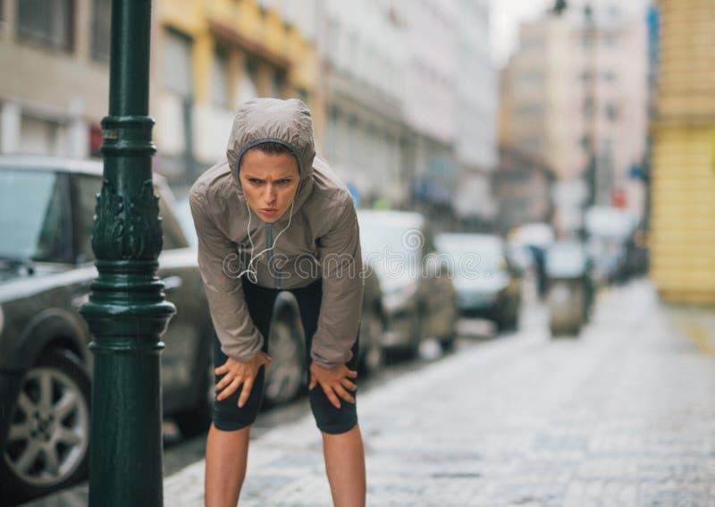 Frauenläufer im Regen, der einen Bruch und ein Ausdehnen nimmt stockfotografie