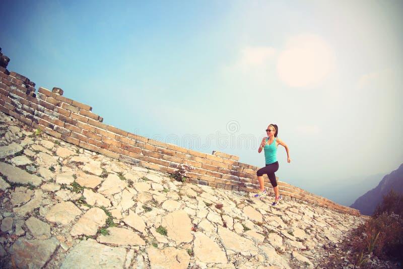 Frauenläuferathlet, der auf Spur an der chinesischen Chinesischen Mauer läuft lizenzfreies stockfoto