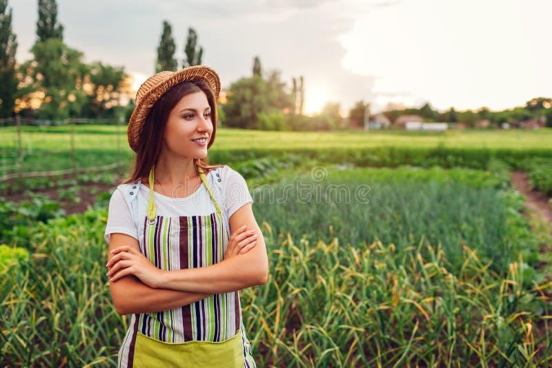 Frauenlandwirt, der Gemüse auf Küchegarten in der Landschaft betrachtet Landwirtschaft und Landwirtschafts-Konzept lizenzfreie stockfotos