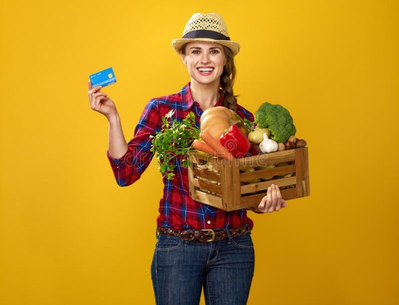 Frauenlandwirt mit Kasten Frischgemüse, das Kreditkarte zeigt stockbilder