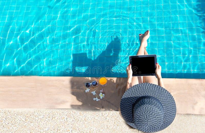 Frauenlebensstilspiellaptopentspannendes nahes Luxusswimmingpool sunbath, Sommertag am Strandurlaubsort im Hotel stockfoto