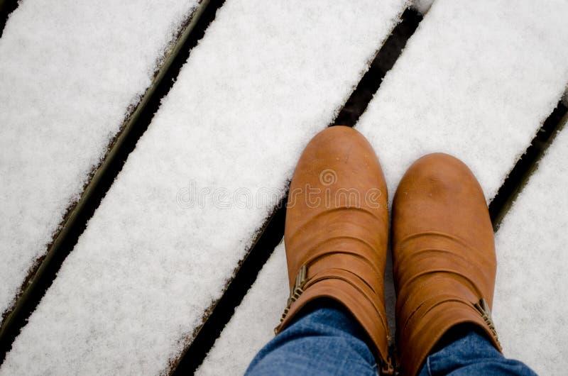 Frauenlederstiefel im Schnee stockfotografie