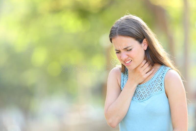 Frauenleidenhalsschmerzen in einem Park stockbild