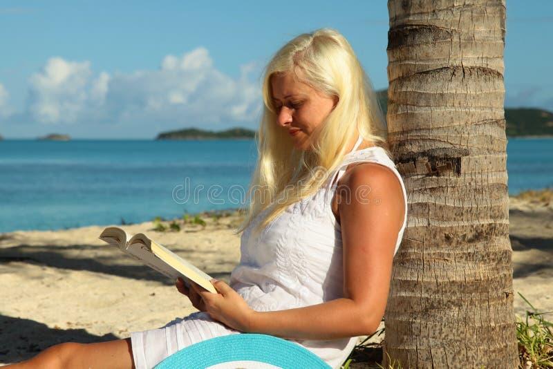 Frauenlesebuch auf dem Strand lizenzfreies stockfoto