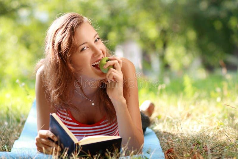 Frauenlesebuch am Park lizenzfreies stockfoto