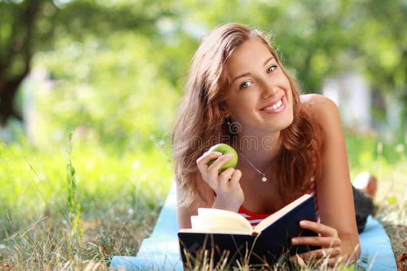 Frauenlesebuch am Park lizenzfreie stockfotografie