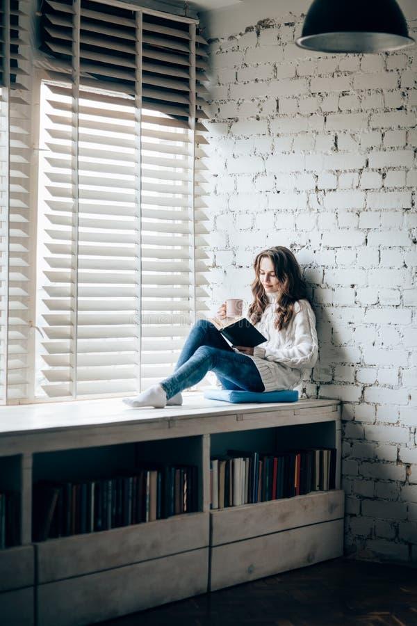 Frauenlesebuch und trinkender heißer Kaffee, die auf Fenster sil sitzen stockfotografie