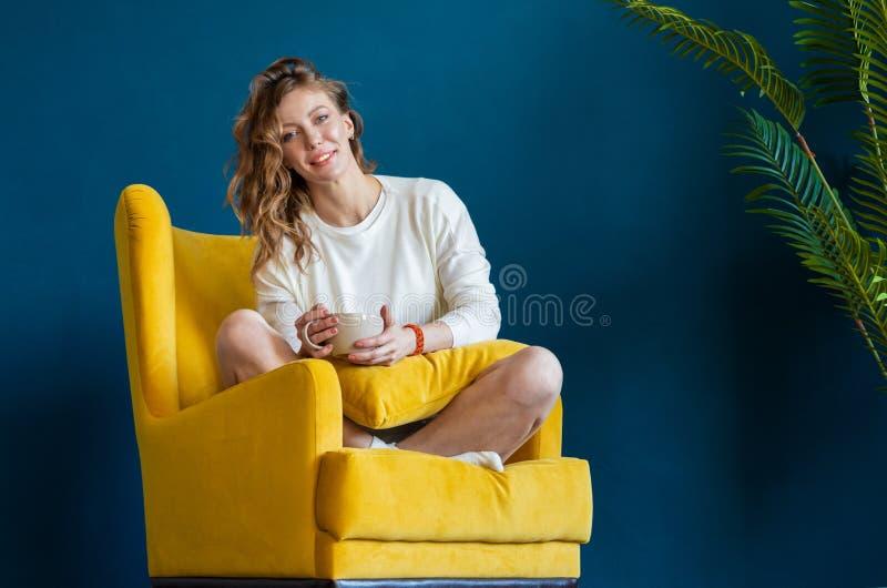 Frauenlesebuch zu Hause, Kaffee oder Tee trinkend und sitzen im Lehnsessel lizenzfreies stockfoto