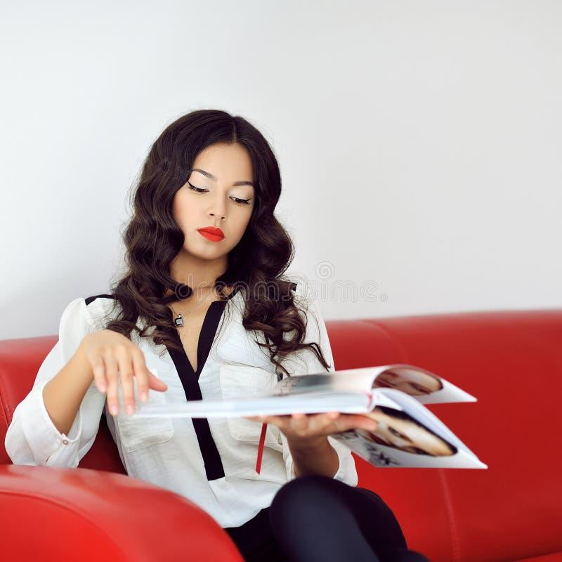 Frauenlesemodezeitschrift zu Hause lizenzfreie stockbilder