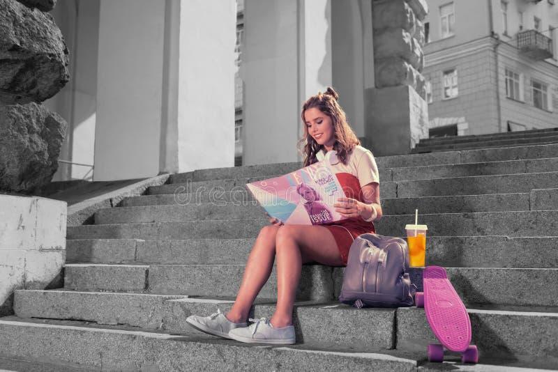 Frauenleseschönheitszeitschrift, nachdem Saft Skateboard gefahren worden ist und getrunken worden ist lizenzfreies stockfoto