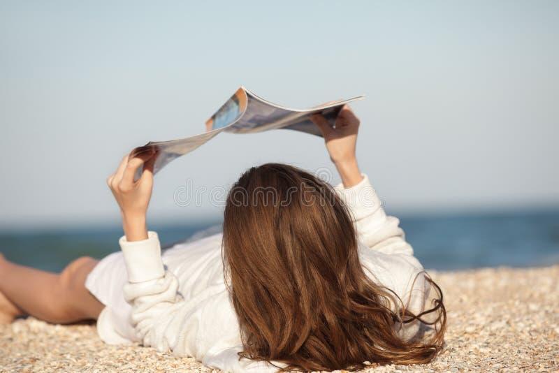 Frauenlesezeitschrift auf Strand lizenzfreies stockbild