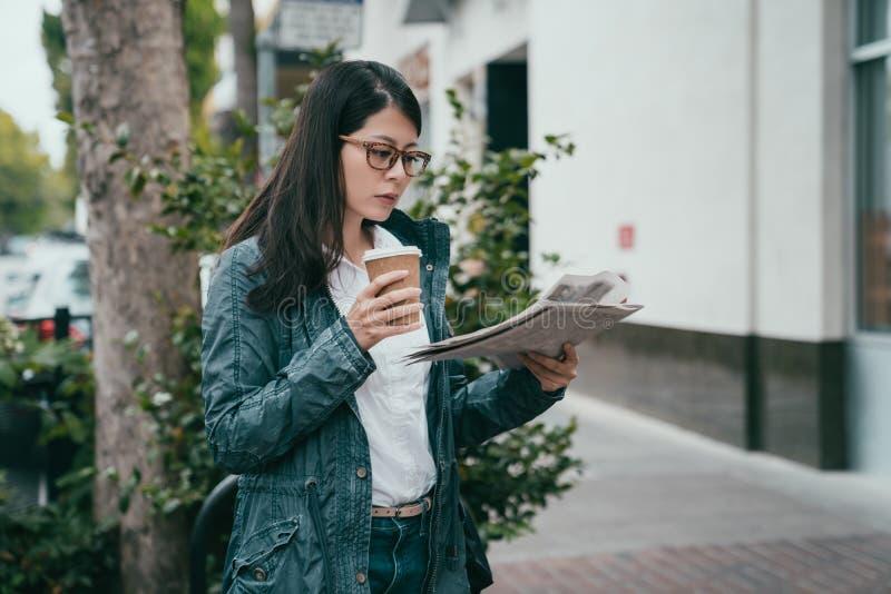 Frauenlesezeitung beim Trinken des Kaffees lizenzfreie stockbilder