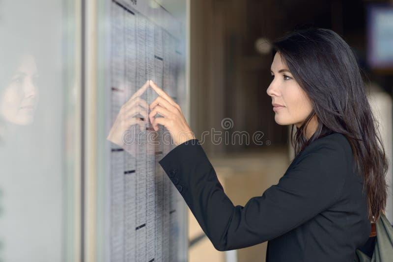 Frauenlesezugzeitplan stockfotos