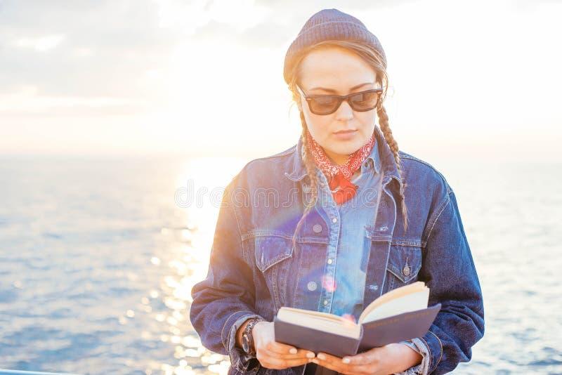 Frauenlesung auf Küste stockbilder