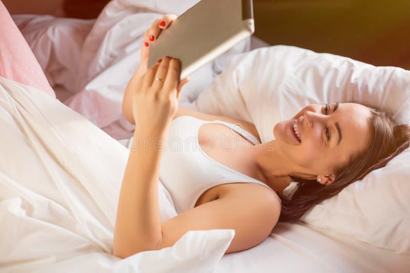Frauenlesungs-ebook auf digitaler Tablette im Bett lizenzfreie stockbilder