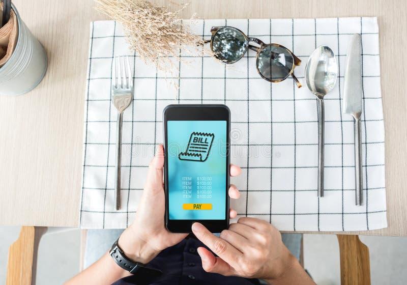 Frauenlohnlebensmittel über bewegliche apps am Restauranttisch Bewegliche Zahlung stockbilder