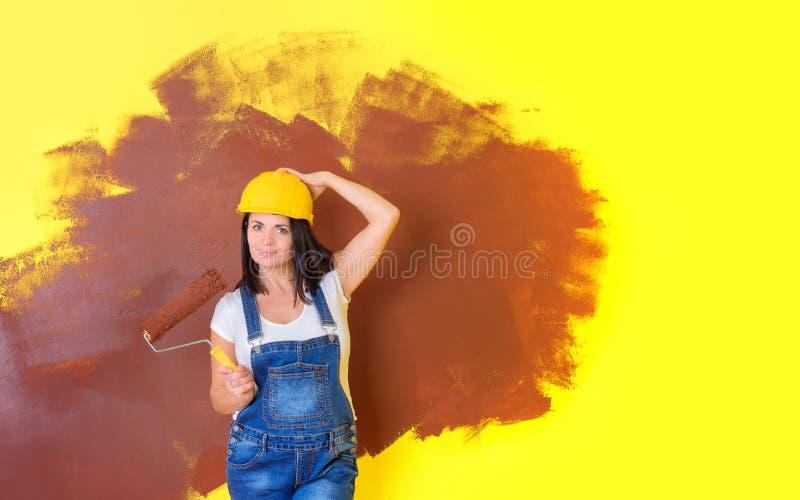 Frauenmaler in einem Bausturzhelm mit einer Farbenrolle stockfoto