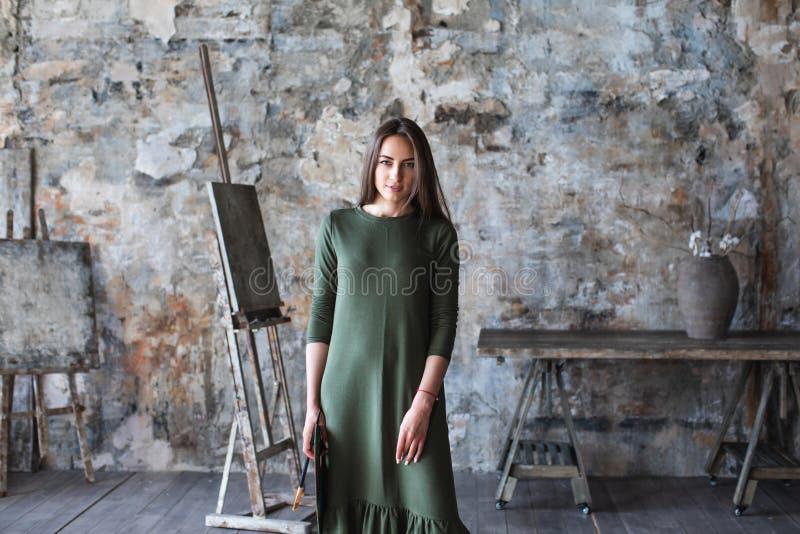 Frauenmaler in einem grünen Kleid mit einer Bürste und einer Palette fotografiert in einem Kunststudio lizenzfreie stockfotos