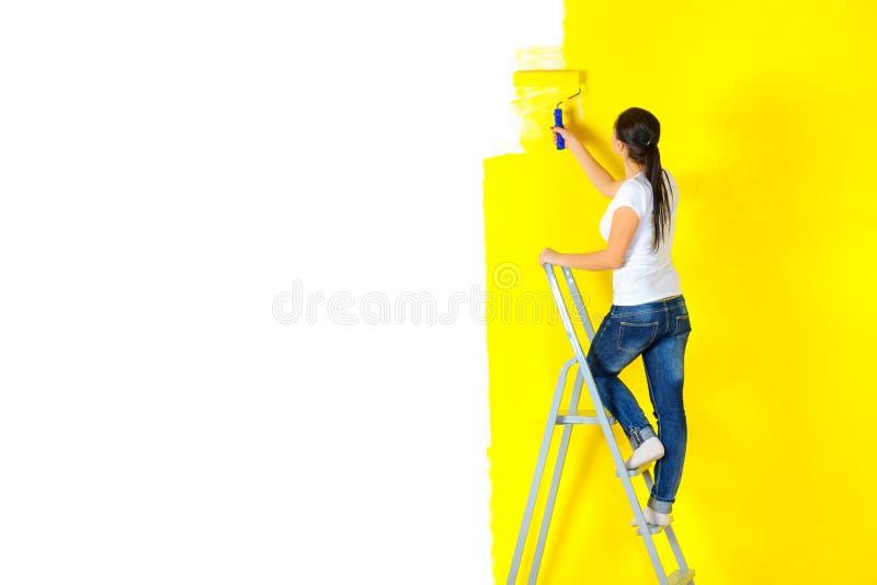 Frauenmaler malt aufmerksam die Wand mit einer Plattenstellung auf der Treppe lizenzfreie stockfotografie