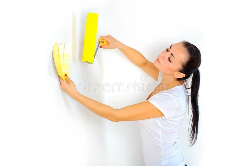 Frauenmaler mit einer Rolle in seiner Hand hebt die Farbe auf der Fliesenpalette auf lizenzfreie stockbilder
