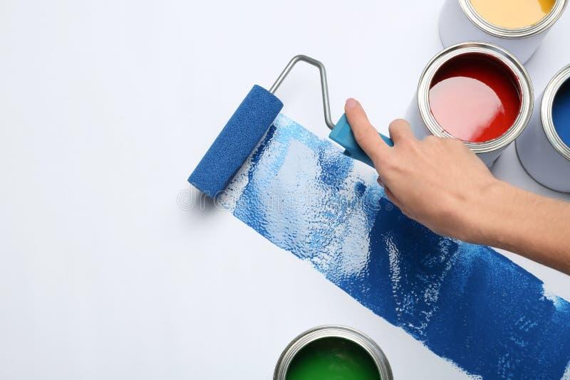 Frauenmalerei mit Rollenbürste nahe Dosen auf weißem Hintergrund stockfoto