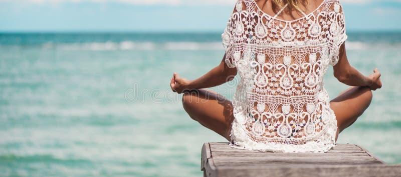 Frauenmeditation in einer Yogahaltung am Strand stockfotografie