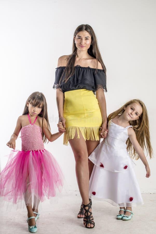 Frauenmode-modell auf der Brücke mit zwei kleinen Mädchen stockfotografie