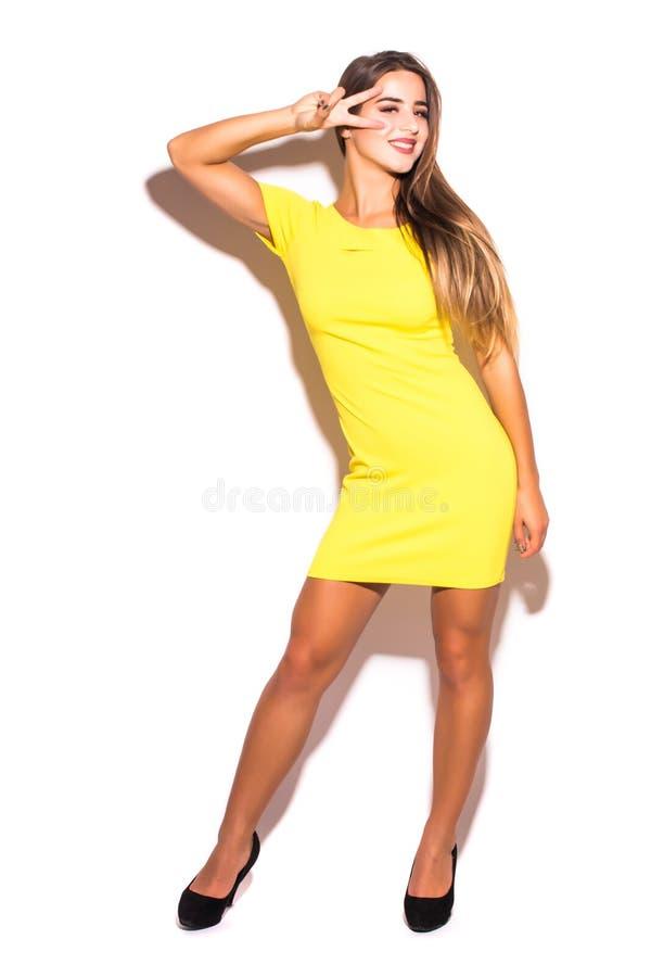 Frauenmode-modell, das im gelben Kleid gegen grauen Hintergrund steht stockbild