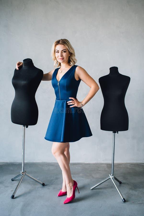 Frauenmodedesigner steht nahe den Mannequins stockbild