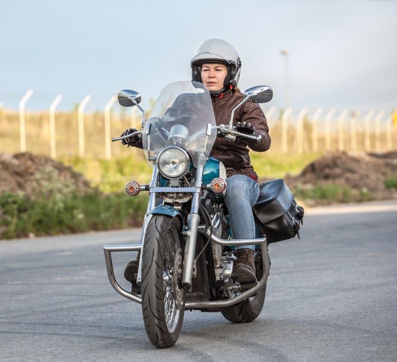 Frauenmotorradfahrer-Reitsolo auf Zerhacker auf Asphaltstadtstraße lizenzfreie stockbilder