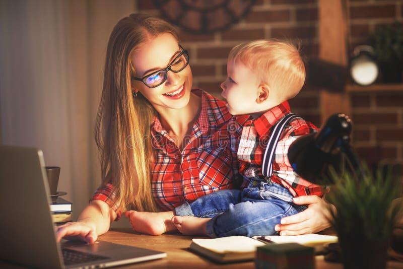 Frauenmutter, die zu Hause mit einem Baby hinter einem Computer arbeitet lizenzfreies stockbild